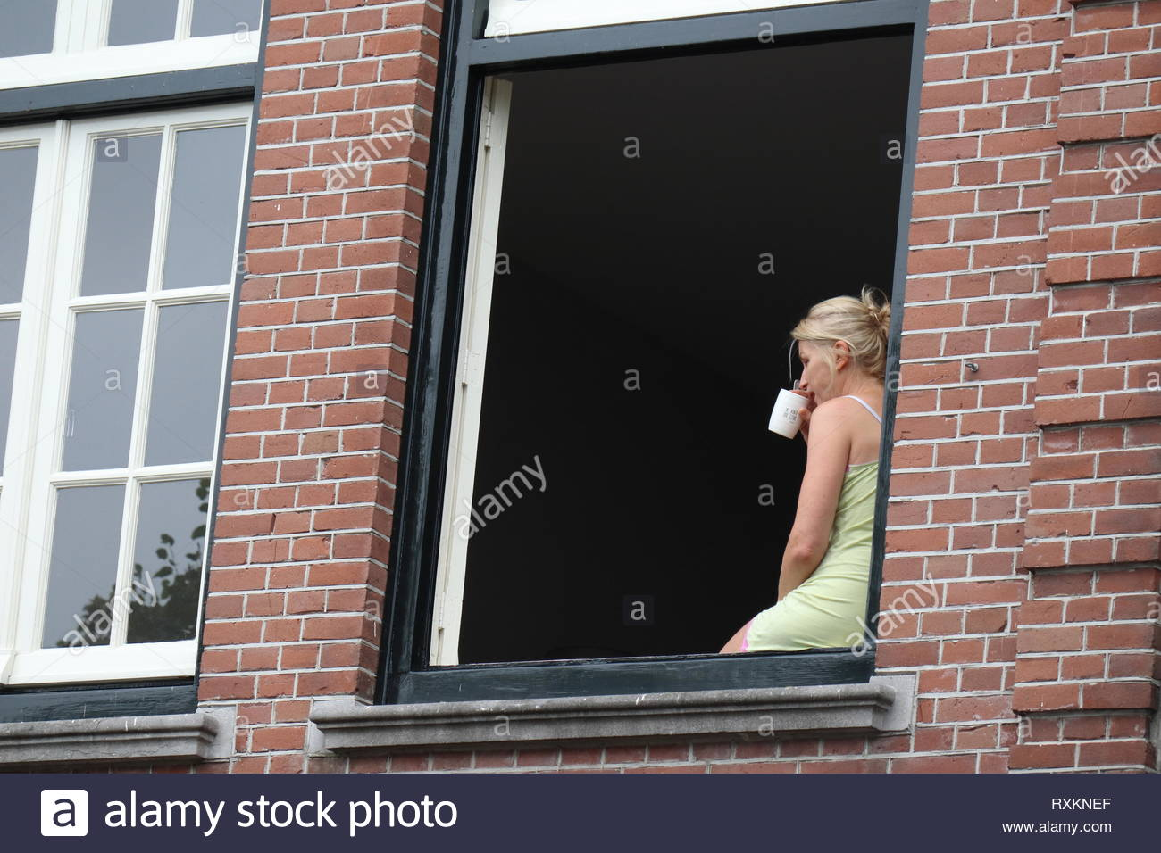 Netherland, Muiden, 8/19/2018: Coffee drinking dutch woman sitting in window after waking up. - Stock Image
