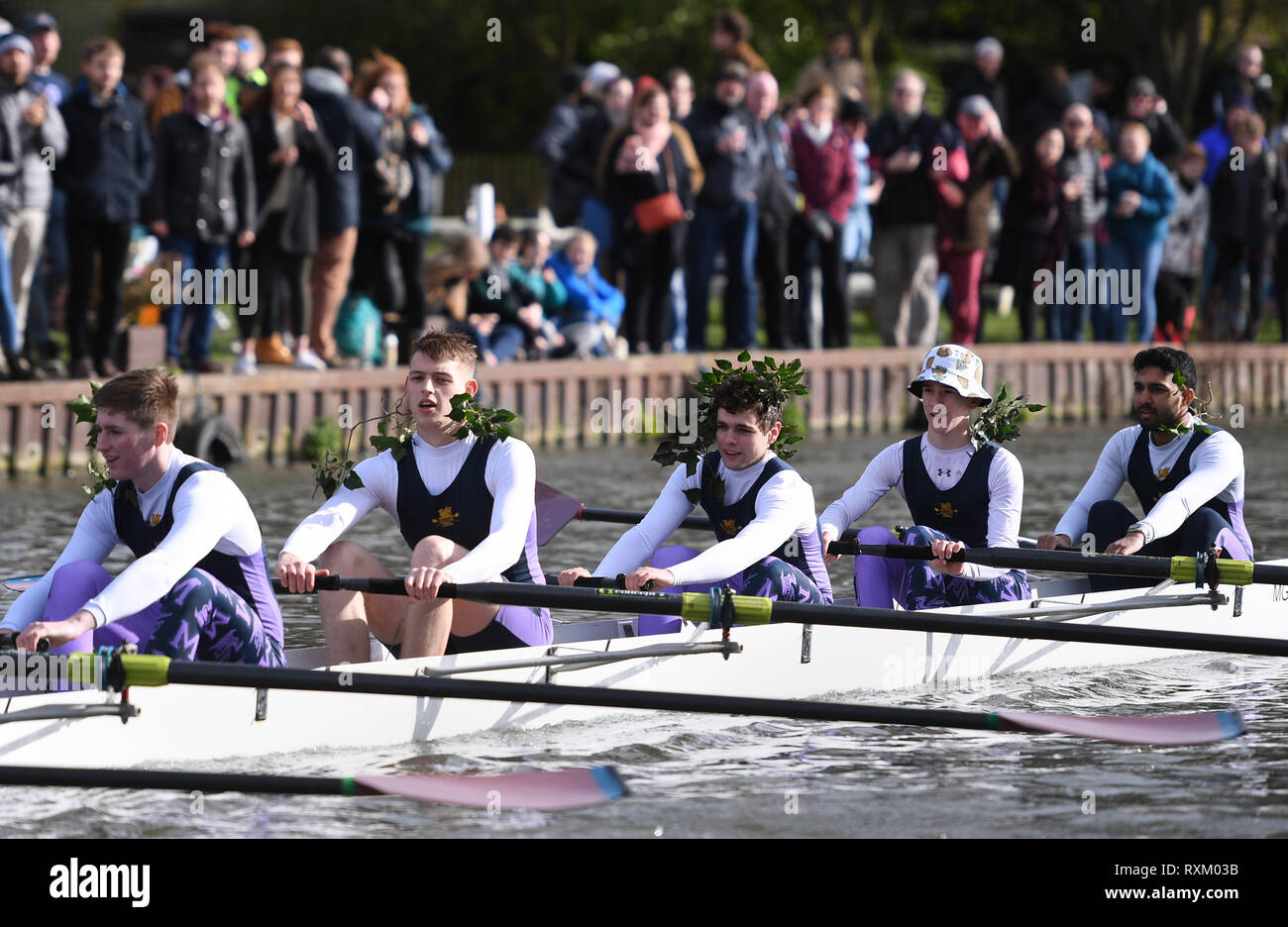 A crew from Magdelene College row home with greenery in their hair to signify a successful bump during the final day of the Cambridge University Lent Bumps along the River Cam in Cambridge. - Stock Image