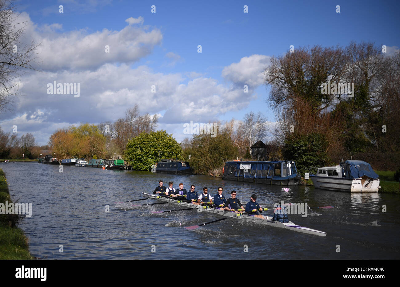 Magdelene College make their way to the start during the final day of the Cambridge University Lent Bumps along the River Cam in Cambridge. - Stock Image