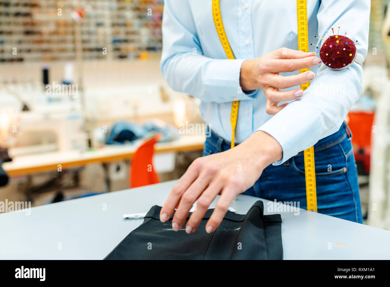 Alterations tailor working on some trousers - Stock Image