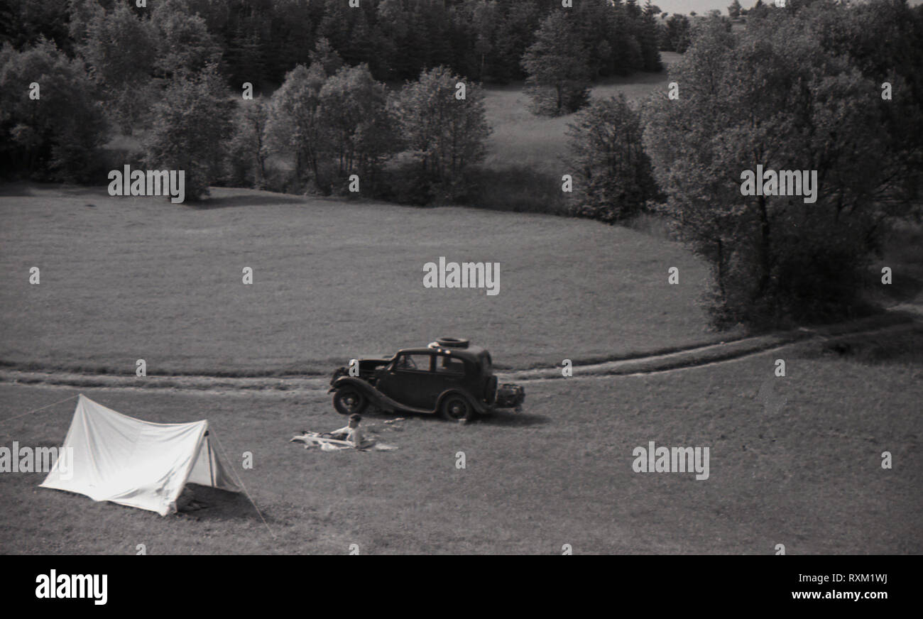 1930s, Sudetenland, Czechoslovakia, touring Europe in the inter-war years, a young man camping, showing his small tent and a car from this era parked in a field. - Stock Image