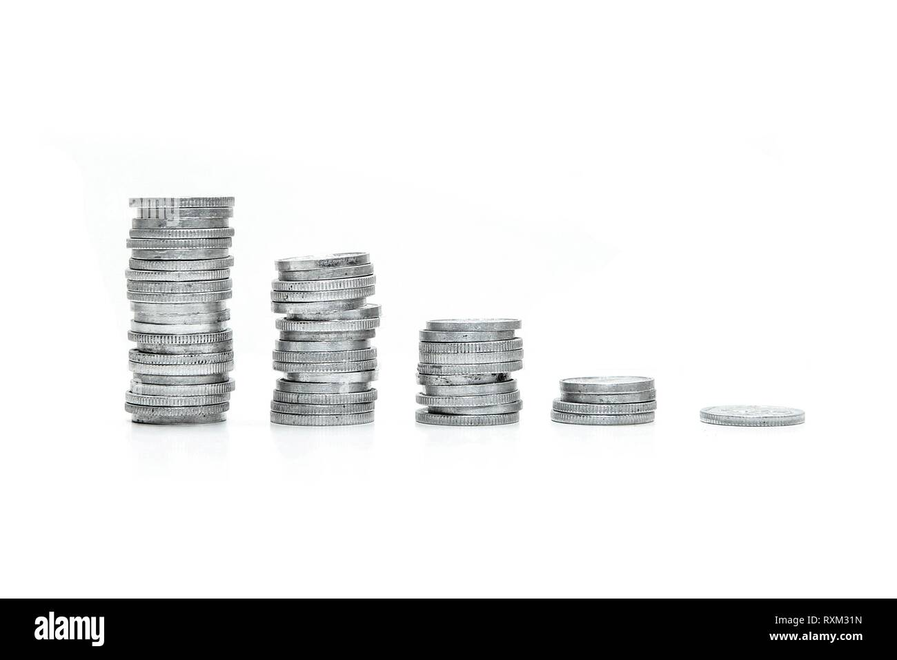 A column of small coins sorted from the highest to the lowest one. Symbolises the decrease of prices. Isolated on white background. - Stock Image