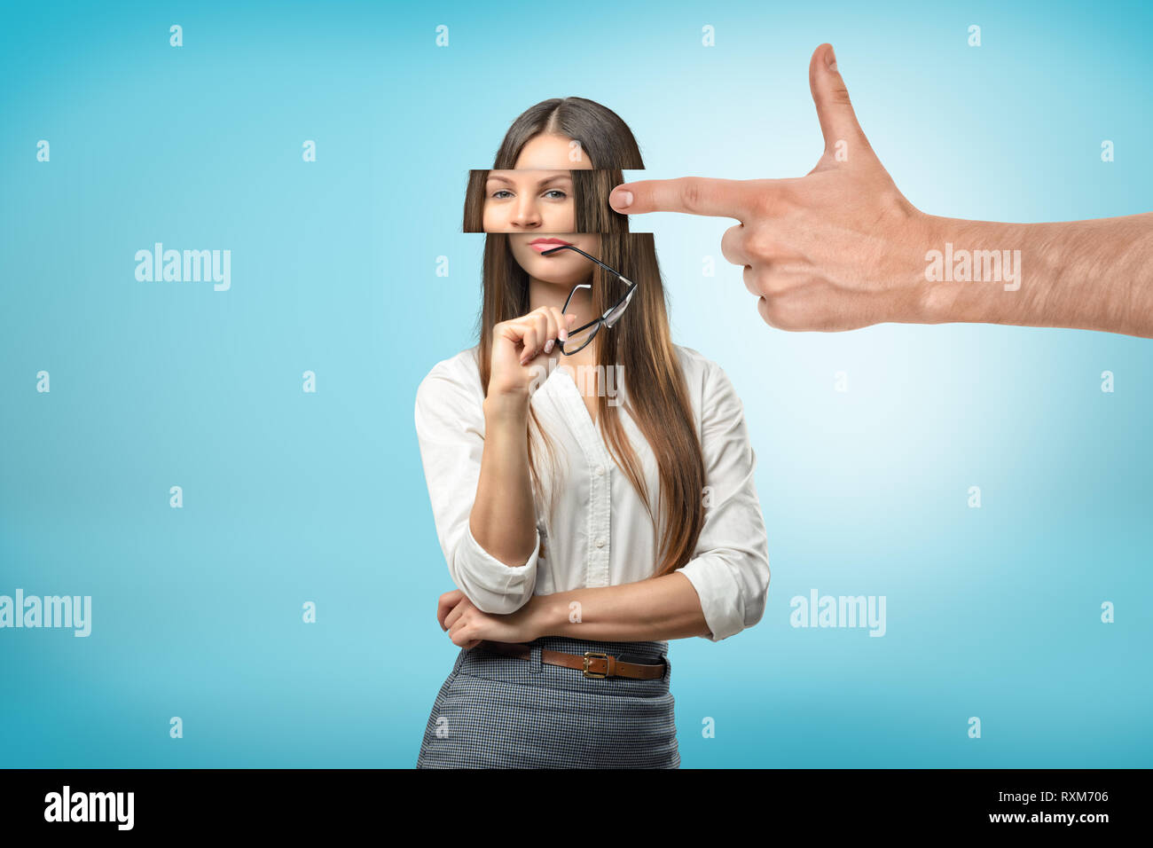 Big male hand with a finger pointing to a young woman with fragmented head on blue background - Stock Image