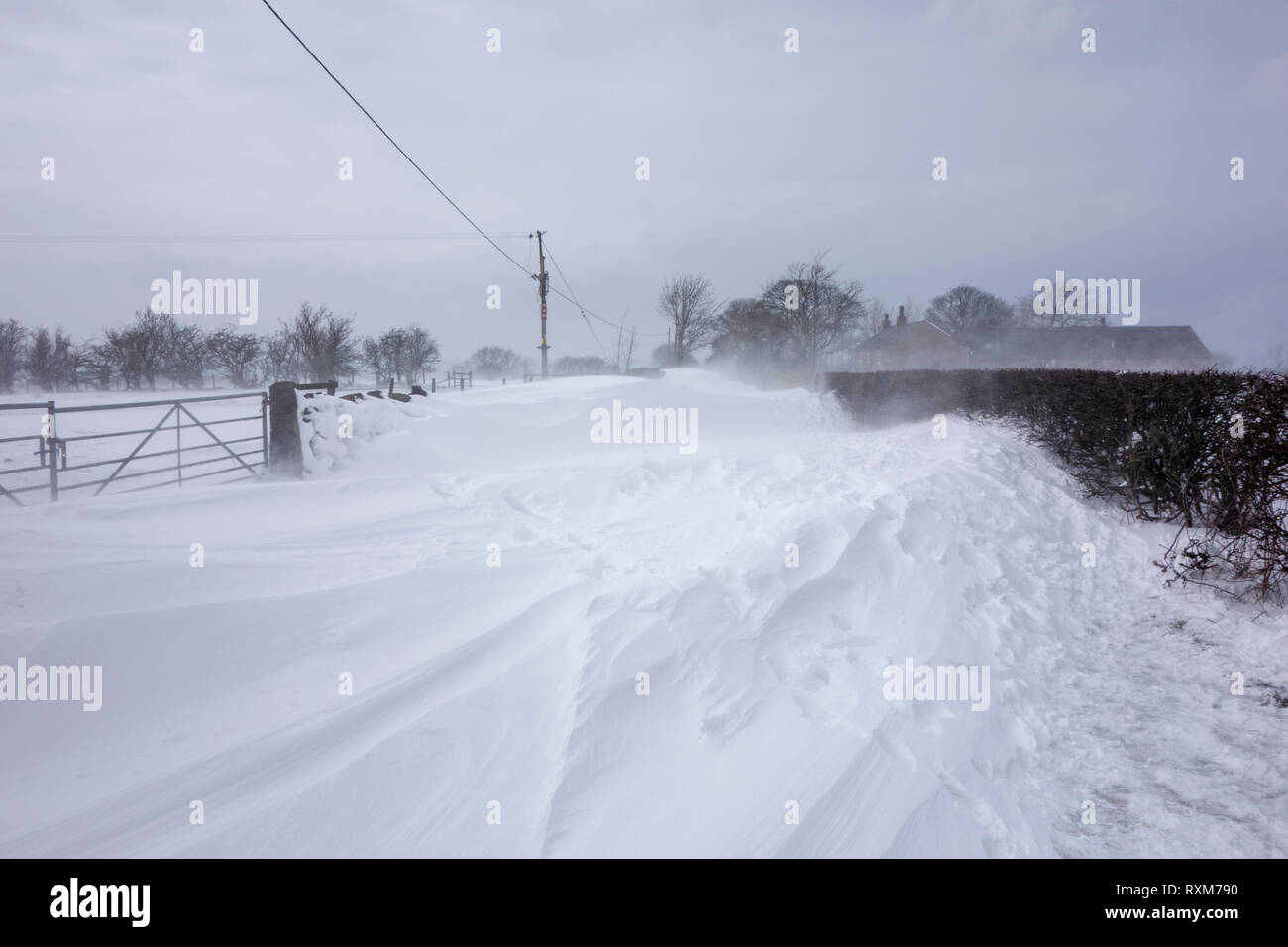 Blizzards and heavy snow fall block a country lane near Chorley Lancashire - Stock Image