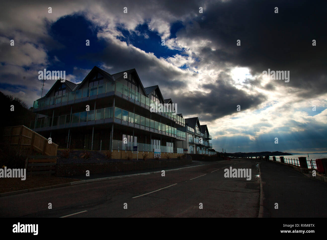 expensive,block,of,seaside,apartments,with,glass,balcony,balconies,dramatic,skies,clouds,Gurnard,Isle of Wight,England, UK, - Stock Image