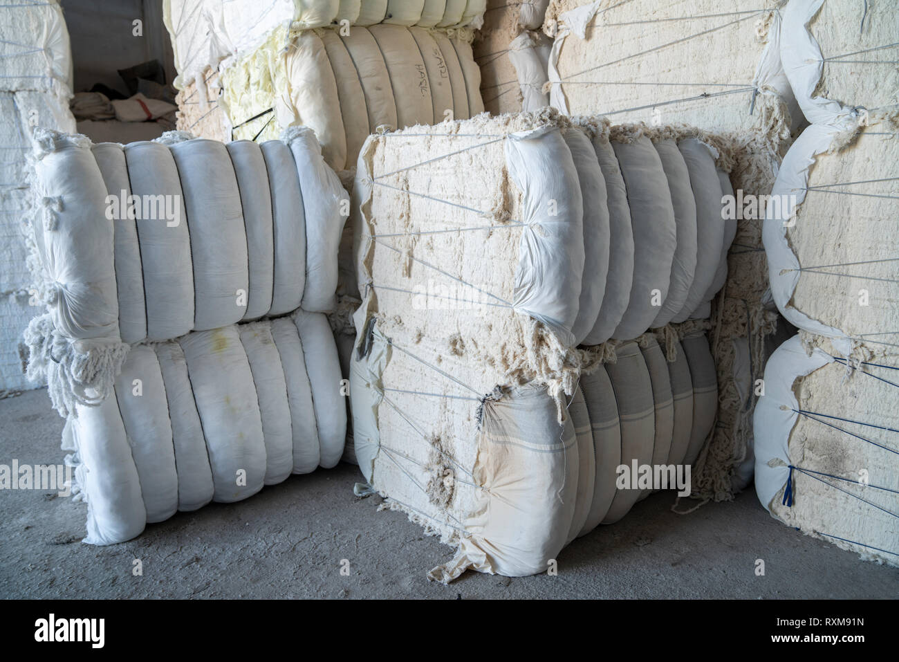 Interior of a storehouse .Stacked waste textile scraps In Bales - Stock Image