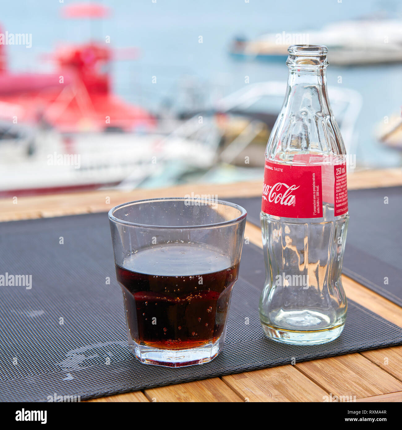 Coca-Cola bottle on a table in the restaurant - Stock Image