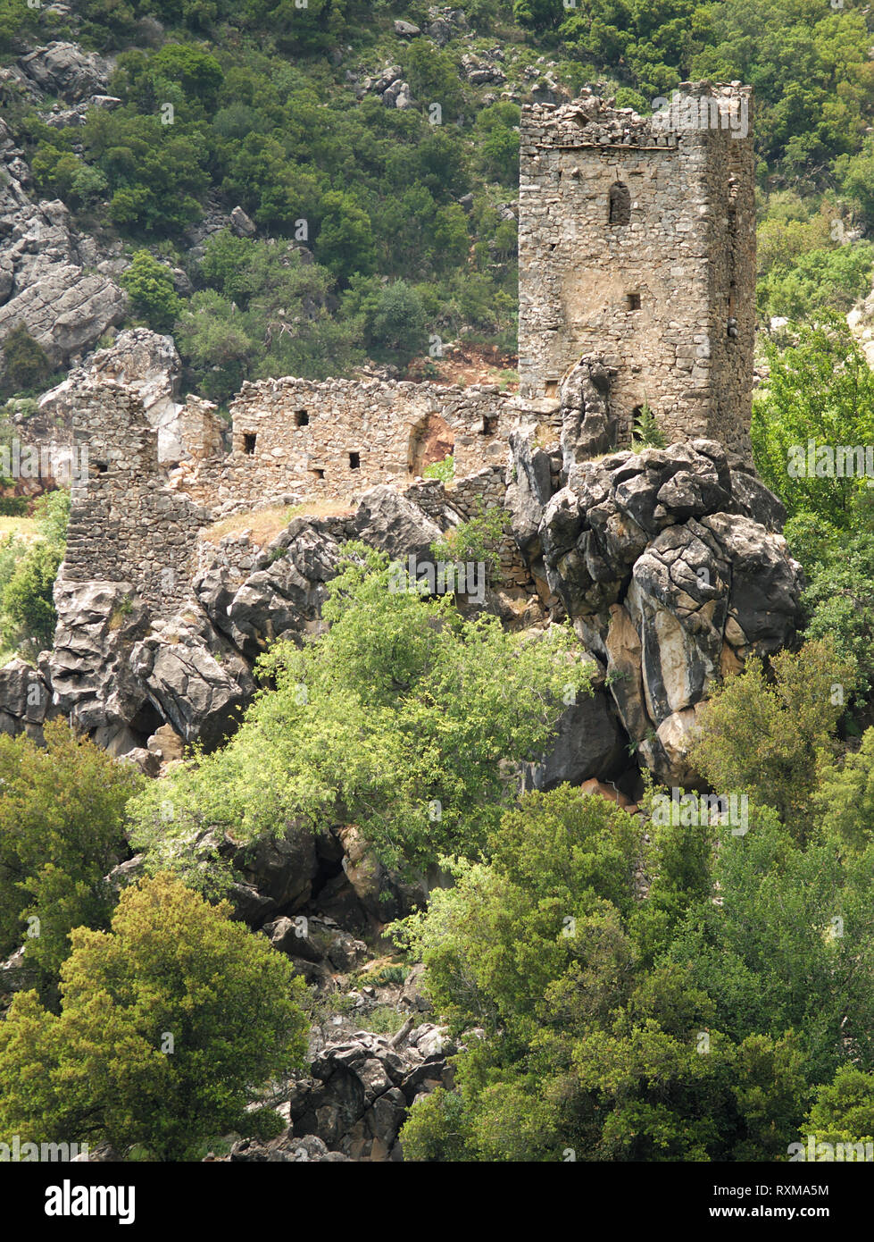 Stone tower ruins on a steep rocky cliff with trees in Mani, Greece. - Stock Image