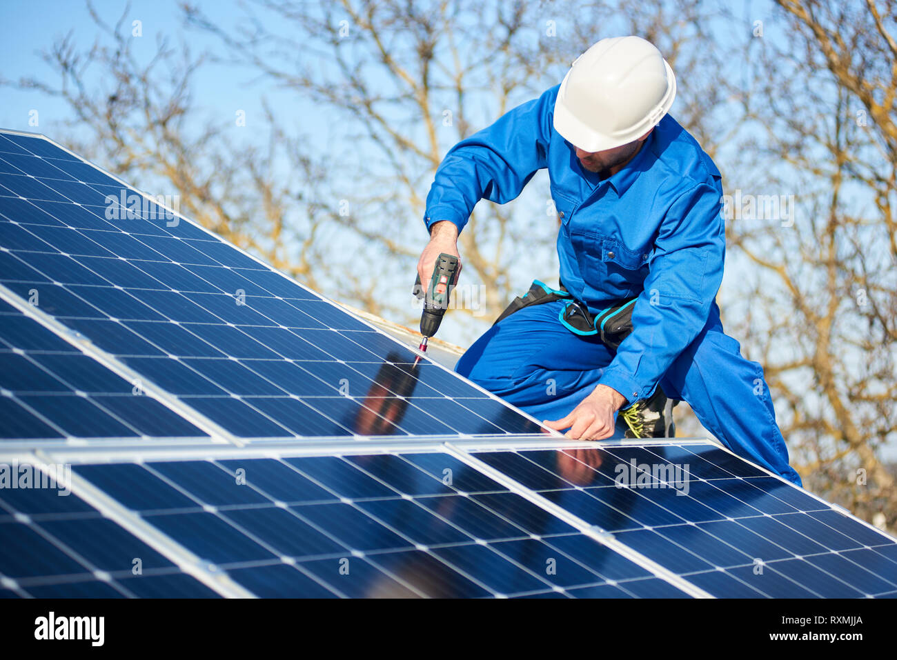 Male engineer in blue suit and protective helmet installing photovoltaic panel system using screwdriver. Professional electrician mounting solar modul - Stock Image