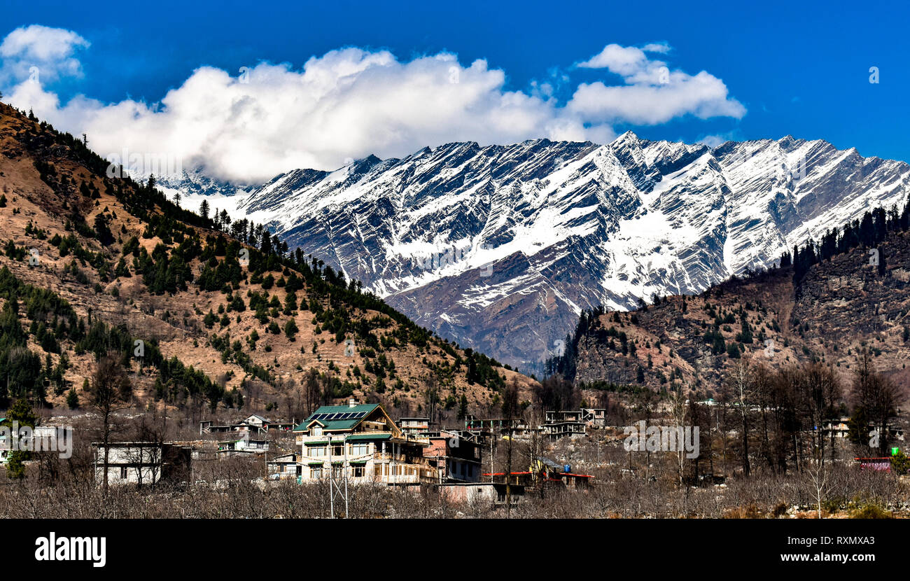 Snow Covered Himalayan Mountain Ranges with Clear Blue sky and White Cumulus Clouds in Manali, Himachal Pradesh, India. A Perfect Summer Destination. - Stock Image