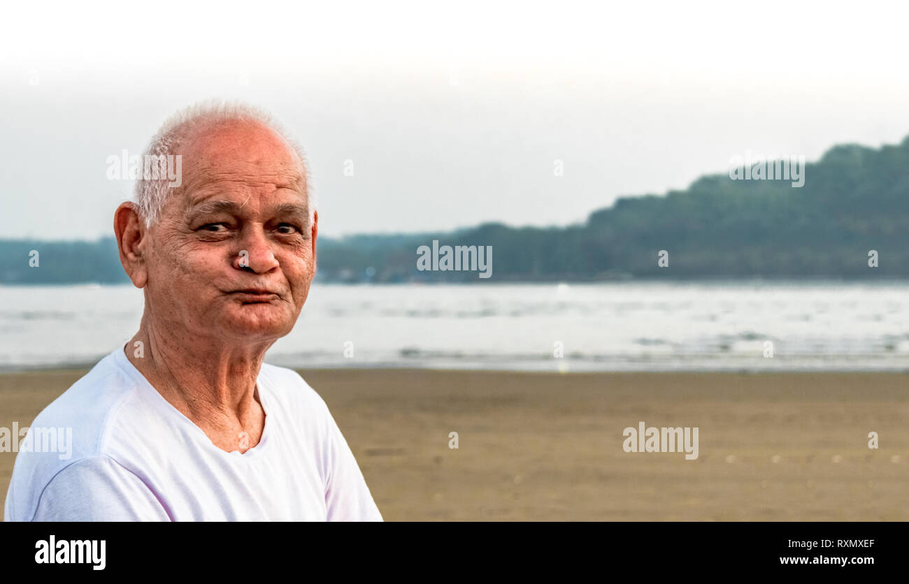 Super Senior Citizen in his mid 80s, posing to camera happily, while making happy faces and enjoying his retired life merrily on a beach - Stock Image
