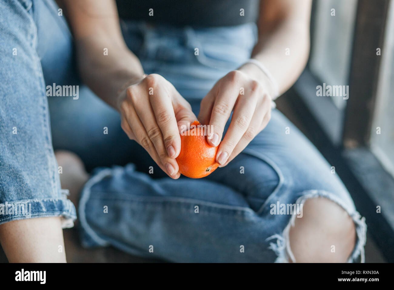 Young girl cleaning tangerine sitting on the windowsill. Close up hands with fresh orange tangerine. Stock Photo