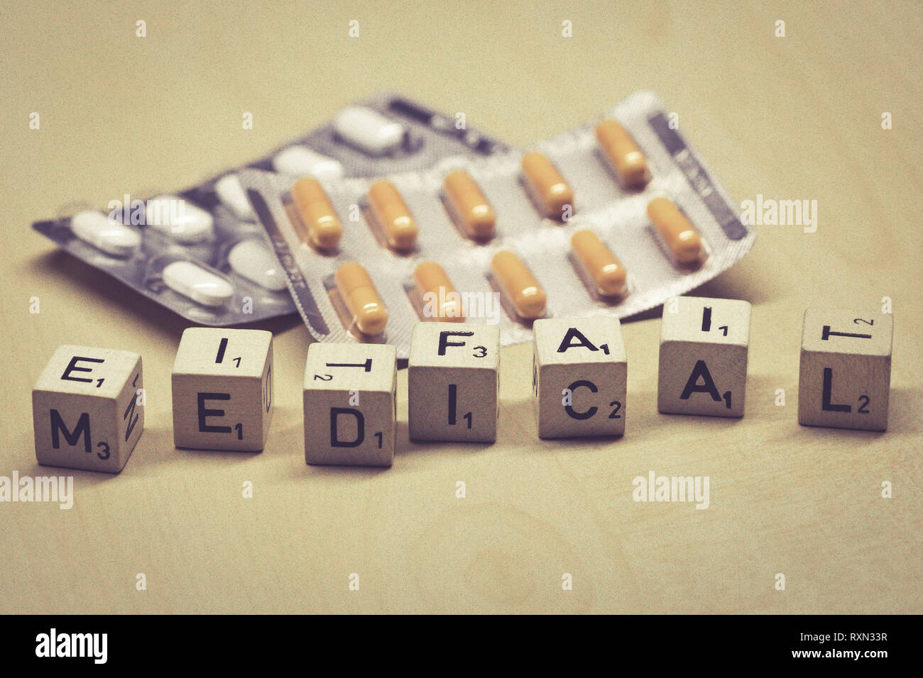 wooden cubes showing the word medical on a table, pills in background - Stock Image