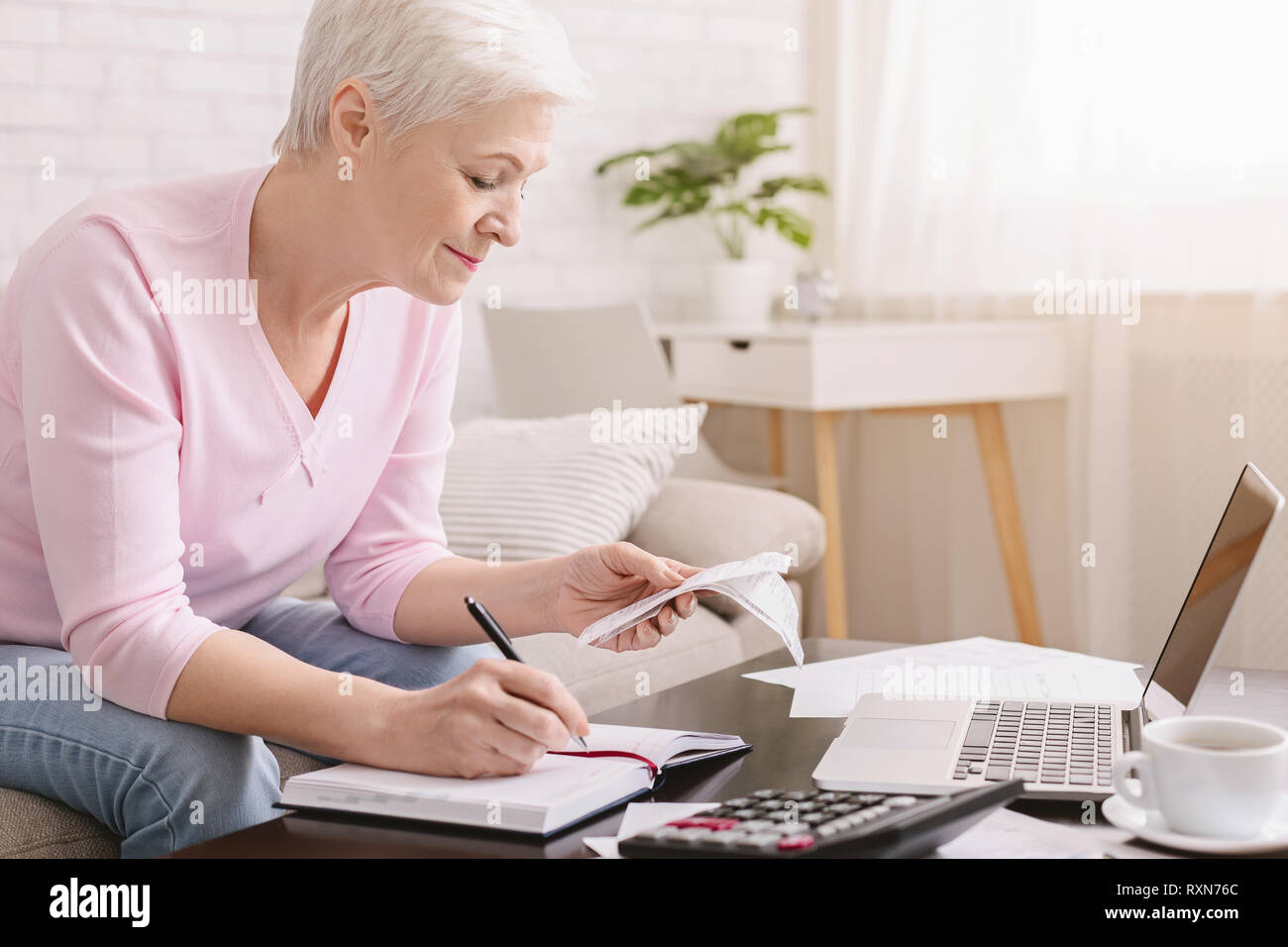 Senior woman bookkeeping bills and payments at home - Stock Image