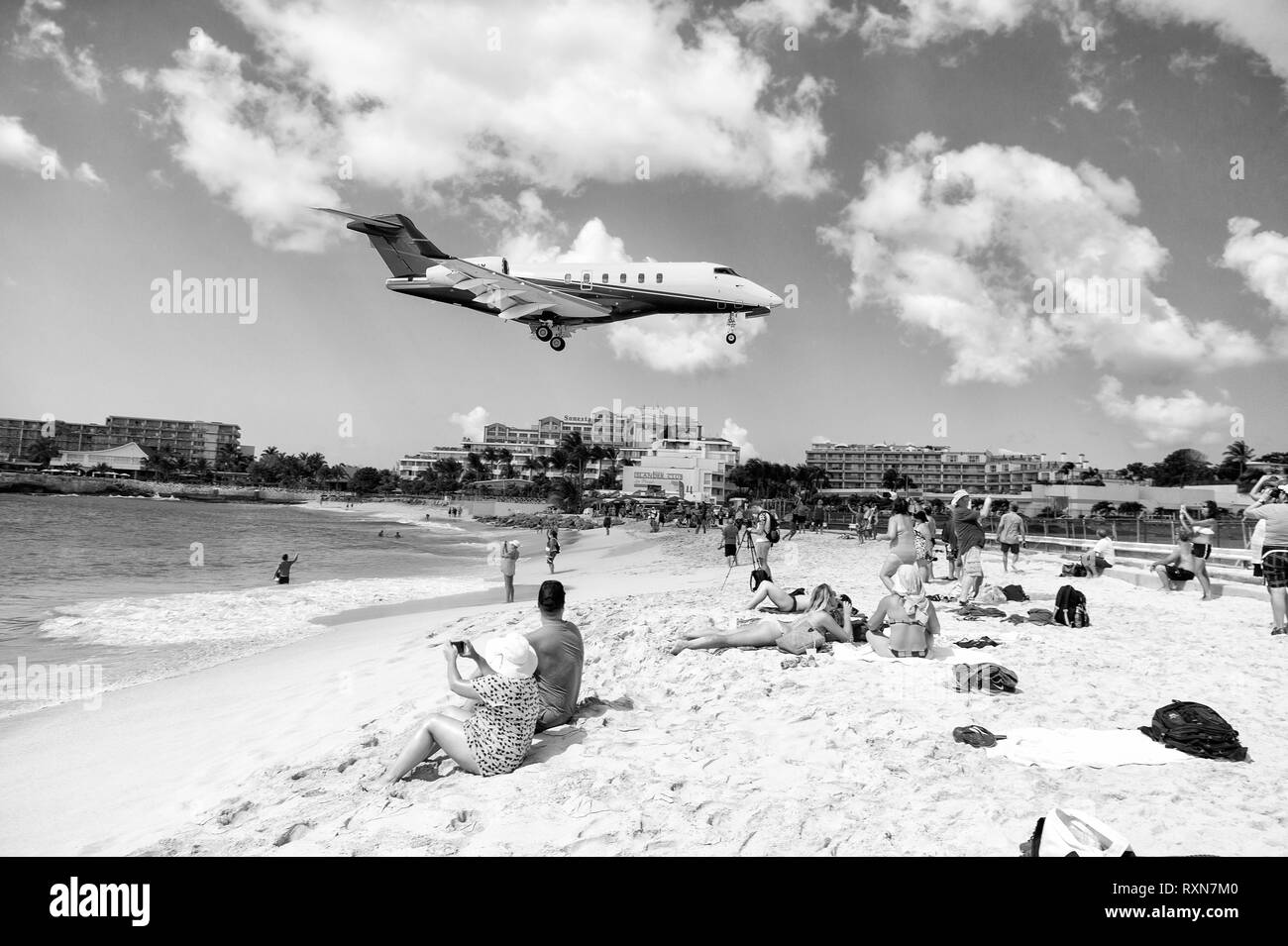 St Maarten, Kingdom of Netherlands - February 13, 2016: beach crowds observe low flying airplanes landing near Maho Beach on island of St Maarten in the Caribbean - Stock Image
