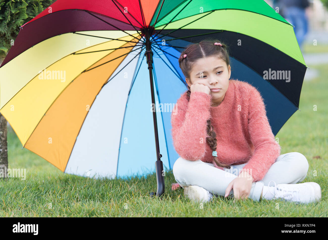 Autumn depression. Spring style. depressive mood in autumn rainy weather. Little girl tired under colorful umbrella. Multicolored umbrella for little happy girl. Rainbow after rain. feeling depressed. - Stock Image