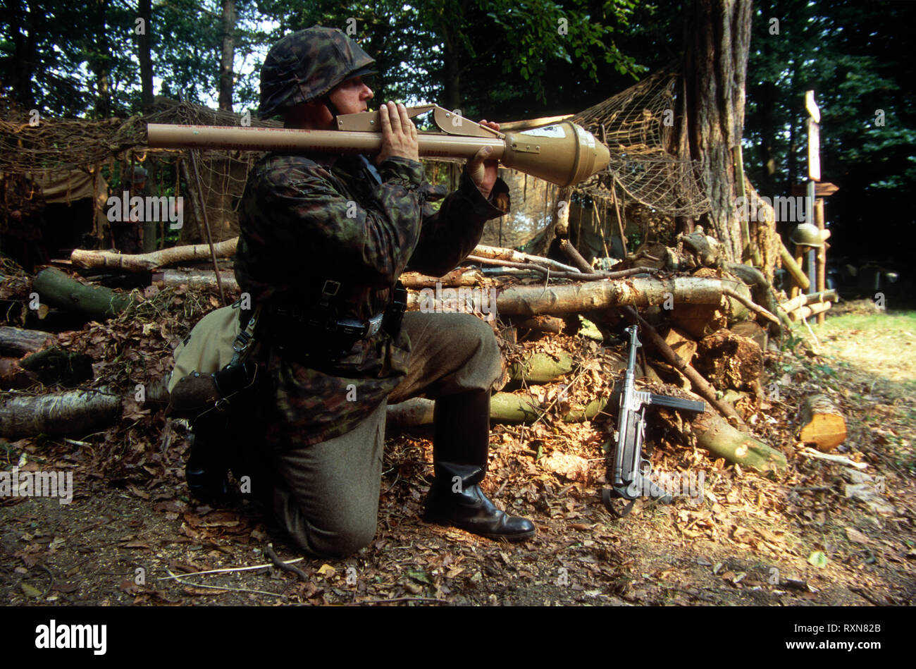 A WW2 Reenactor wears the period uniform of a Waffen SS soldier he fires a Panzerfaust anti tank weapon. - Stock Image