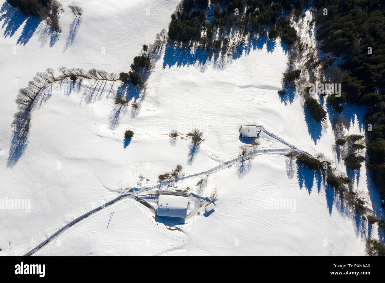 Snow covered remote cottage, homestead in the mountains and snowy road. Aerial drone view - Stock Image
