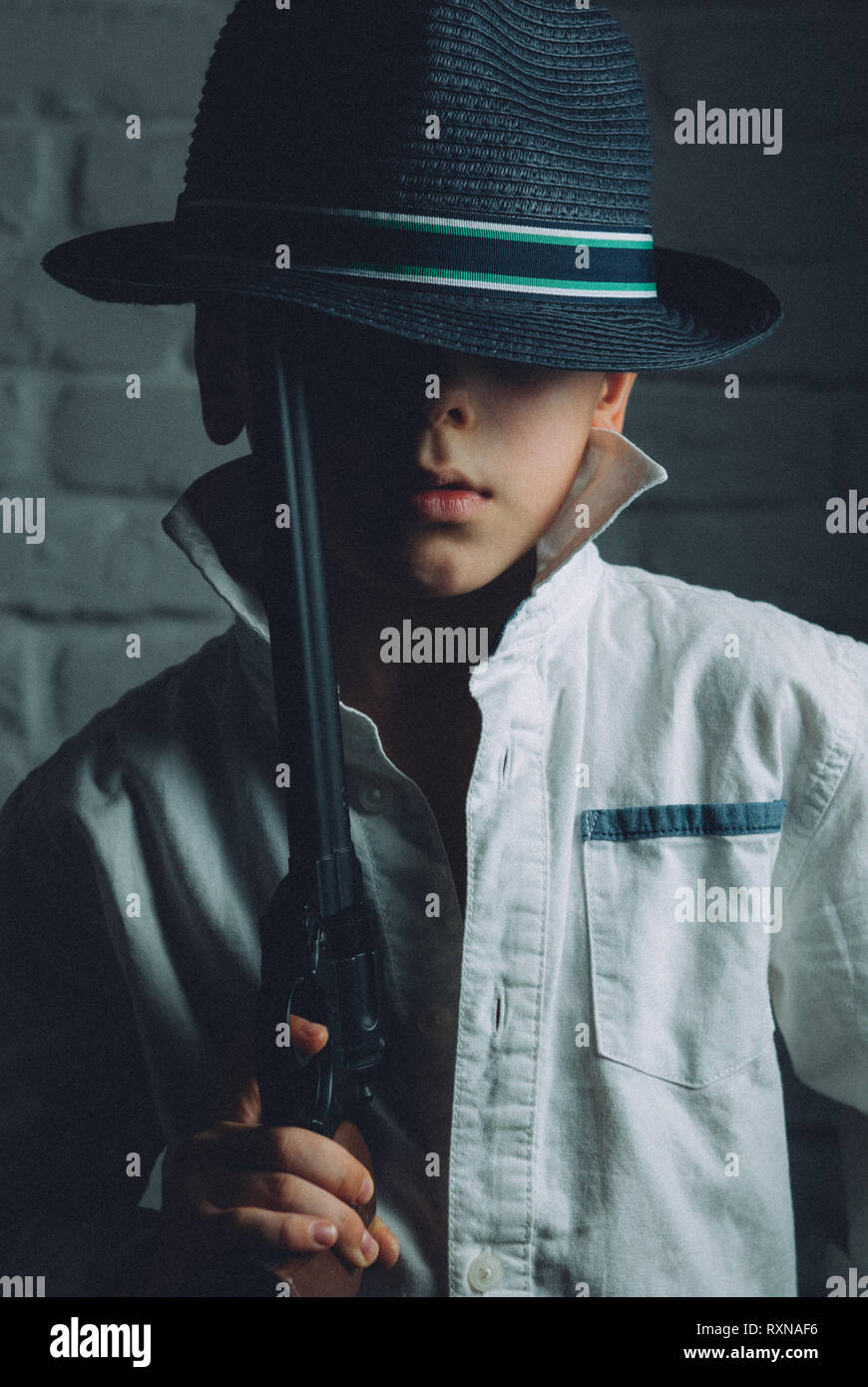 cute little boy wearing vintage hat with long gun in hand in criminal retro style chicago mafia hollywood gangster image - Stock Image