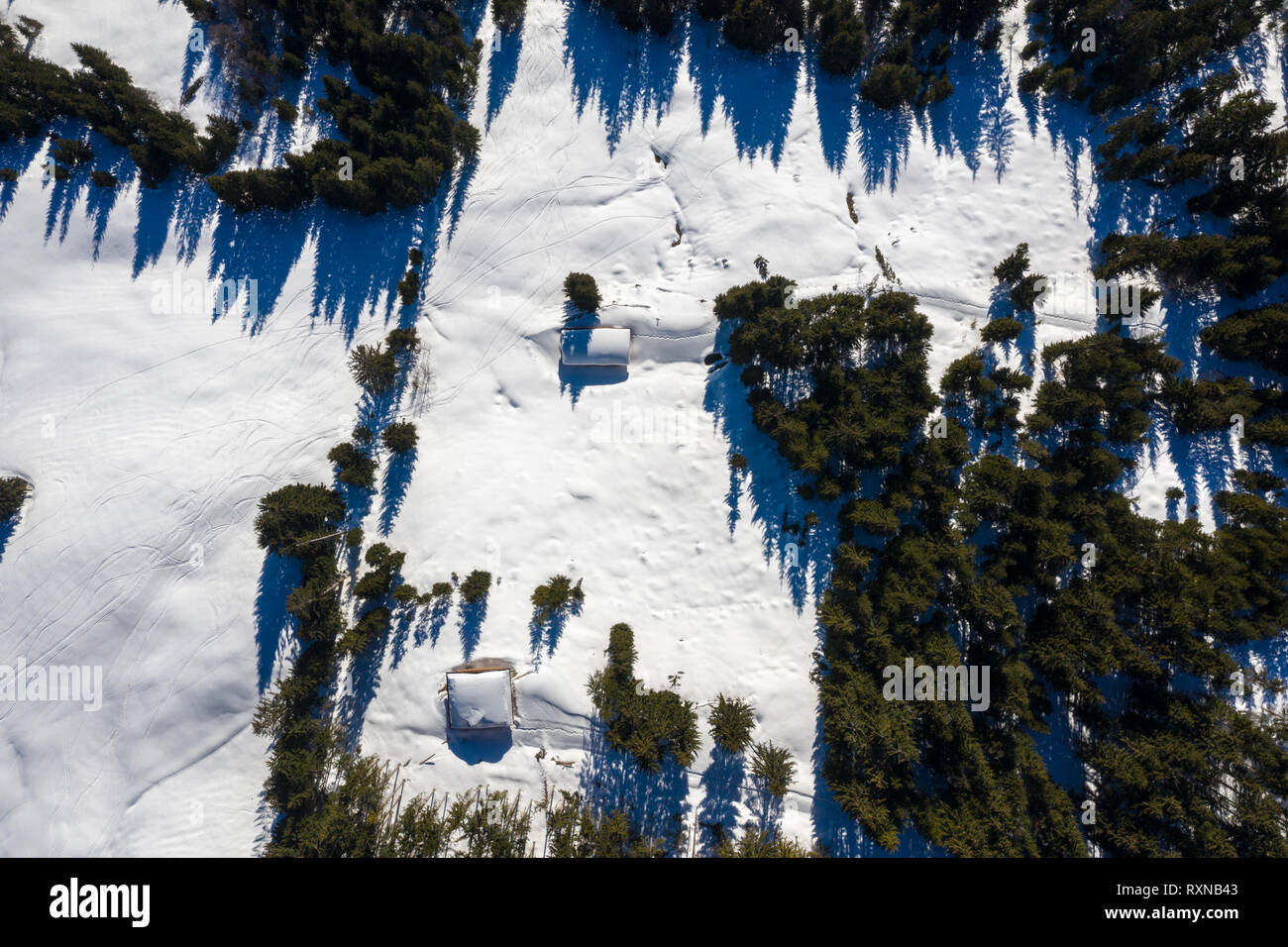 Snow covered remote cottage, homestead in the mountains and snowy sloap. Aerial drone view - Stock Image