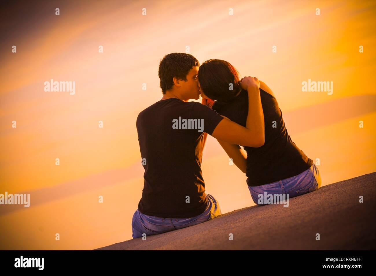 First kiss teen couple in sunset silhouette sunsetlover sunsetaddict sunsetaddicted loving love attractive beautiful female male partner - Stock Image