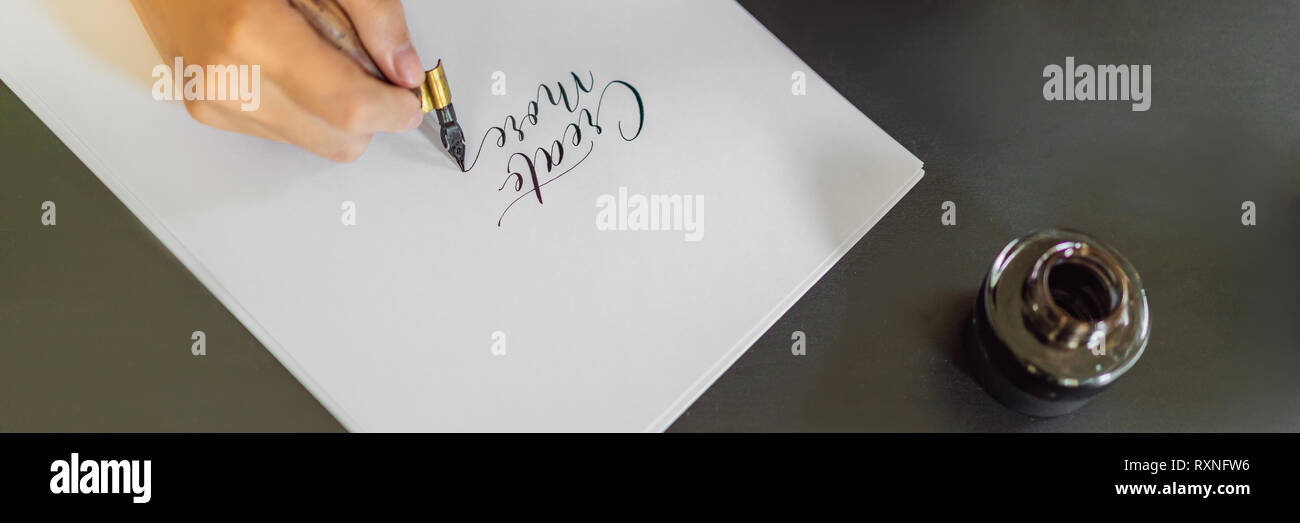 Calligrapher hands writes phrase on white paper. Phrase - Create more. Inscribing ornamental decorated letters. Calligraphy, graphic design, lettering - Stock Image