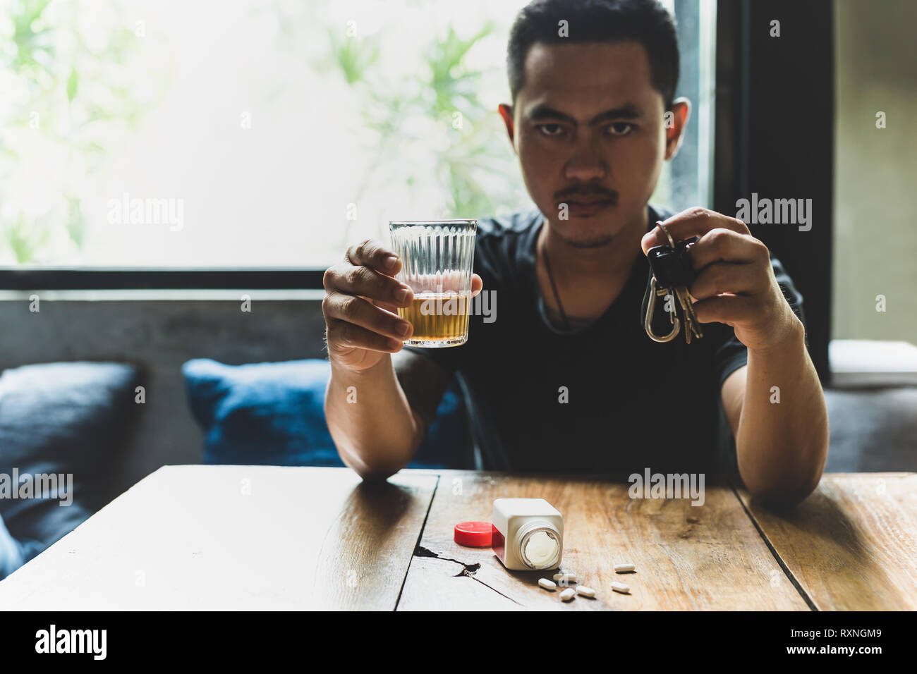 Man holds glass of whiskey and car keys with pills on the table. Stock Photo