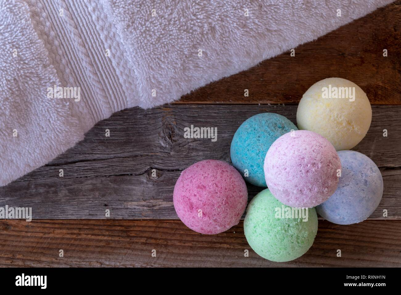 Colorful bath bombs with accessories on weathered wood. - Stock Image