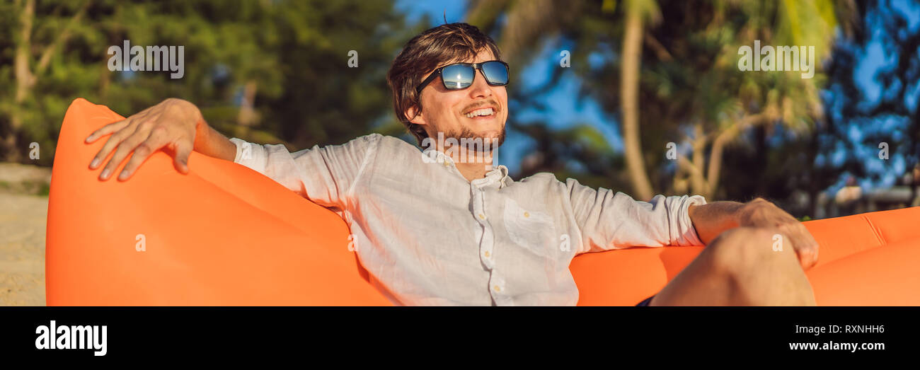 Summer lifestyle portrait of man sitting on the orange inflatable sofa on the beach of tropical island. Relaxing and enjoying life on air bed BANNER - Stock Image