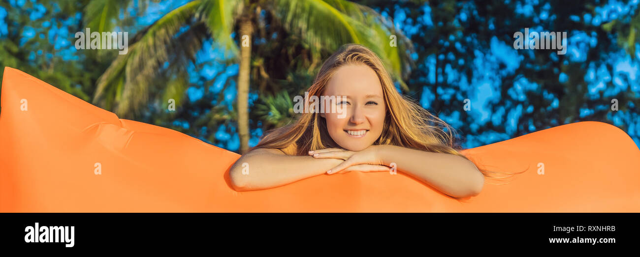 Summer lifestyle portrait of pretty girl sitting on the orange inflatable sofa on the beach of tropical island. Relaxing and enjoying life on air bed