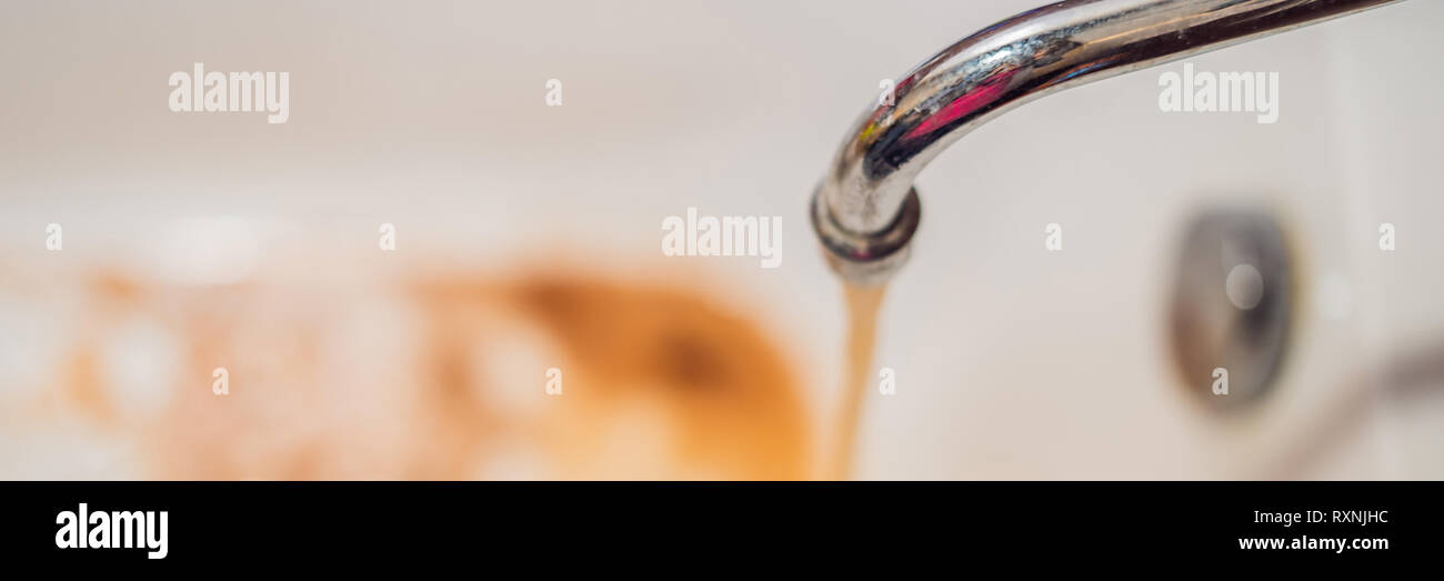 Dirty brown running water falling into a white sink from tap. Environmental pollution concept BANNER, LONG FORMAT - Stock Image
