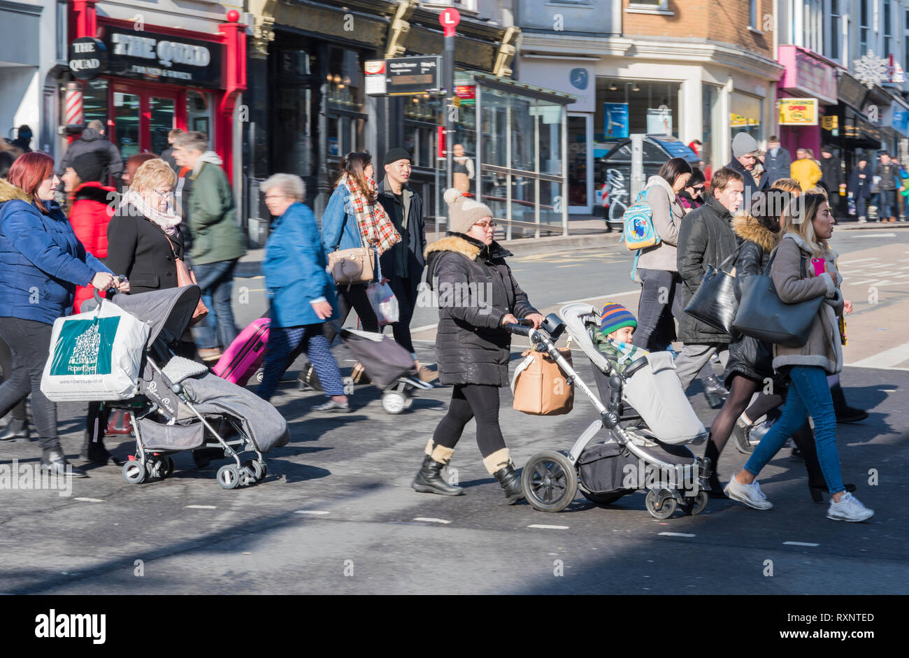 People pushing pushchairs with children across a busy road in Brighton, East Sussex, England, UK. People crossing busy roads. - Stock Image