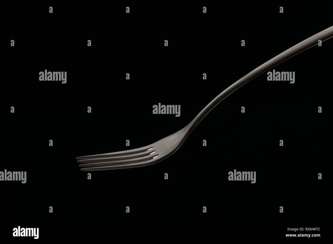 Isolated metal single fork on black background in glowing light, minimalistic abstract cooking concept. Interesting unusual close-up composition. - Stock Image