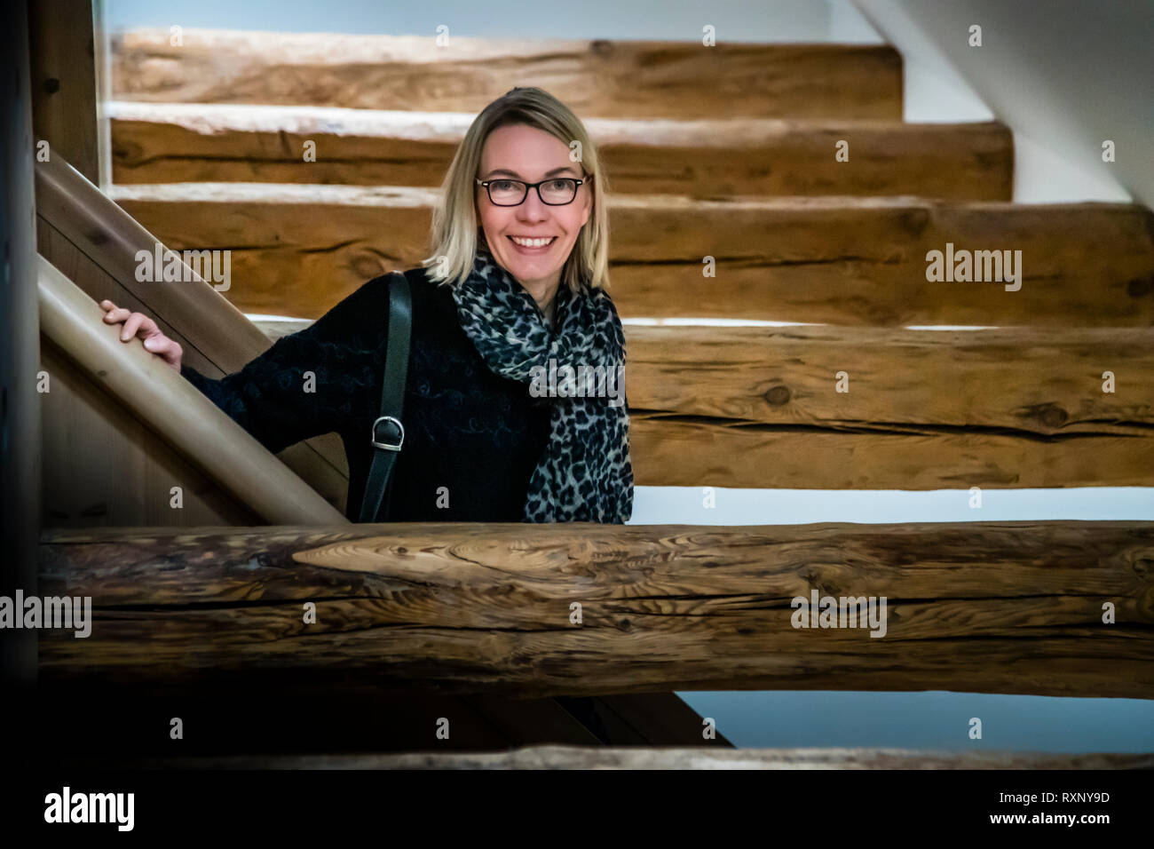 Angela Berg in the middle of the woodwork. In many rooms, the old wooden beams are exposed, set in contrast to modern furniture. Travel journalist Angela Berg at Hotel Kavaliershaus in Fincken, Germany Stock Photo