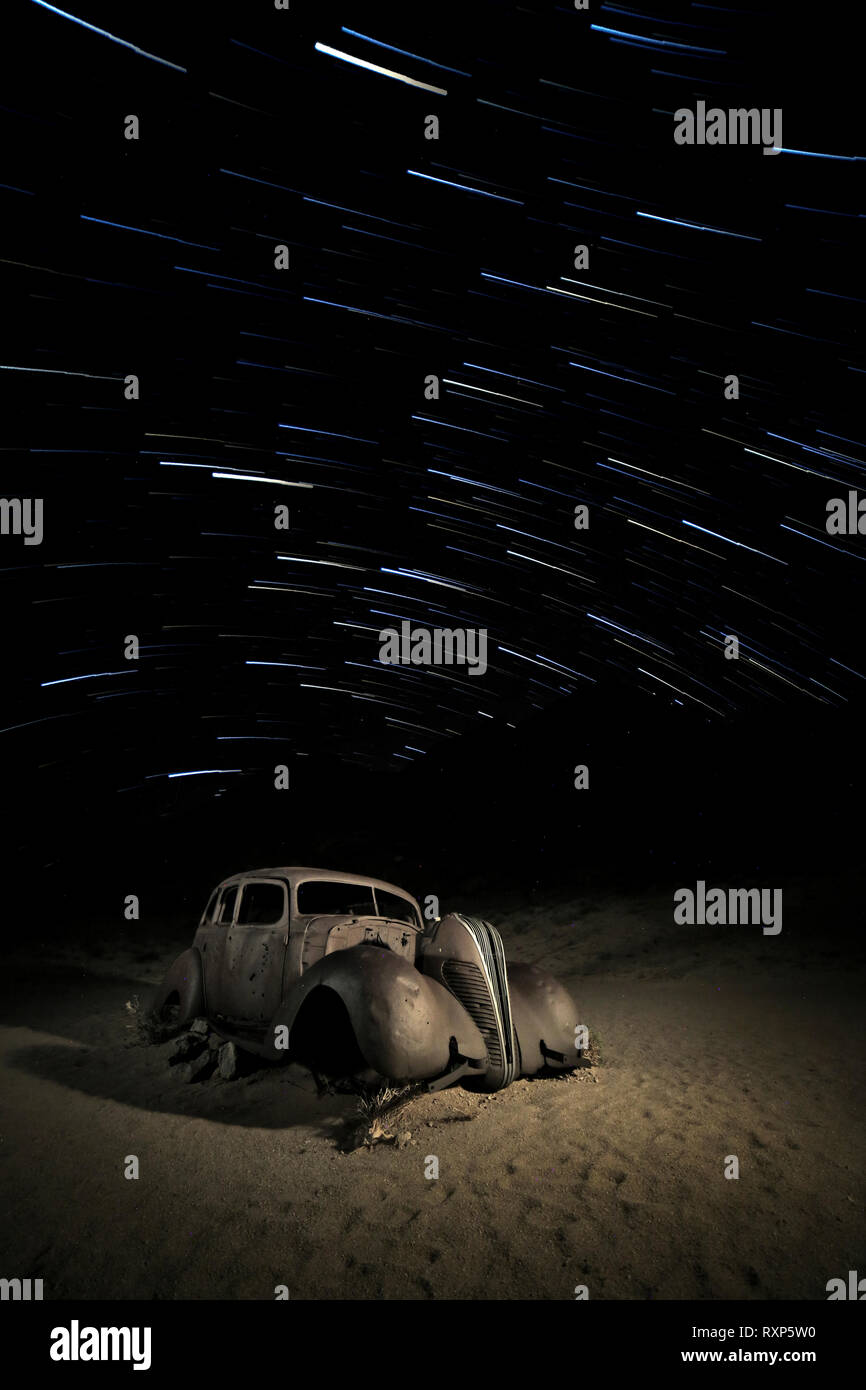 A star trail over an abandoned car - Stock Image