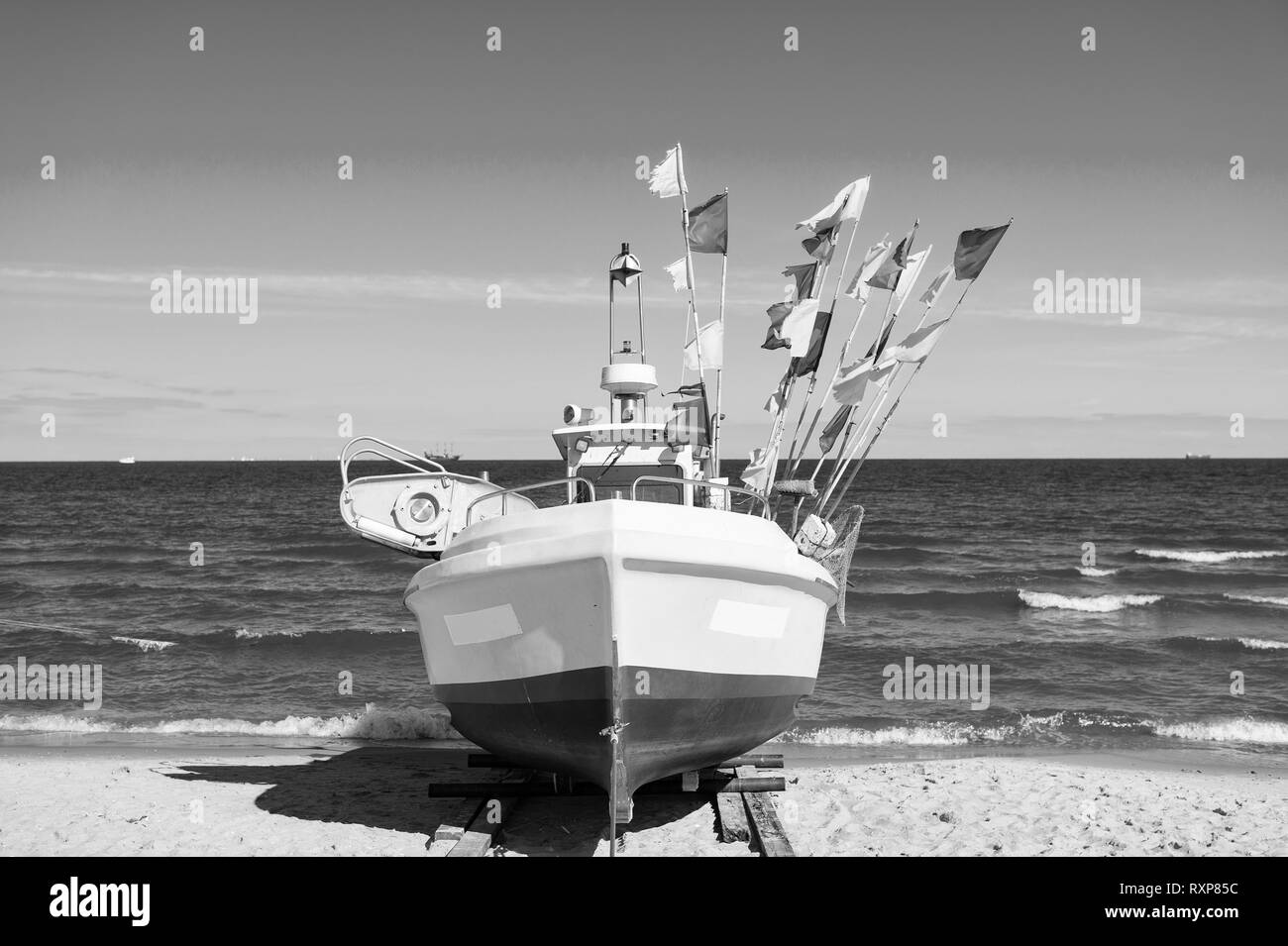 boat or ship modern marine vessel with colorful flags at moorage on beach on sunny day on blue sea and sky background - Stock Image
