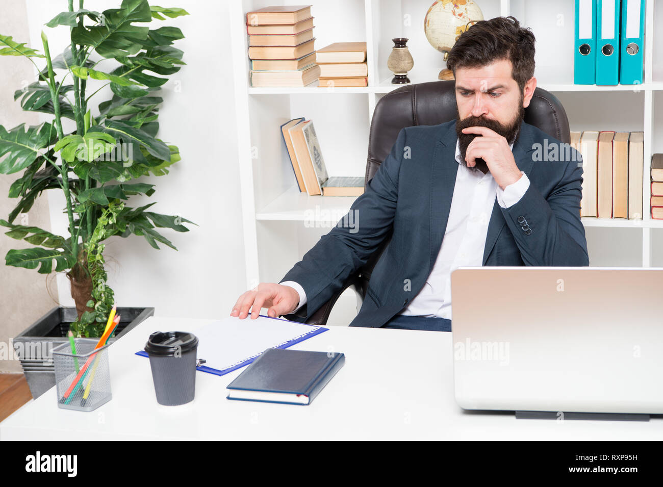 Office routine. Manager solving business problems. Businessman in charge of business solutions. Developing business strategy. Risky business. Man bearded hipster boss sit office with laptop. - Stock Image