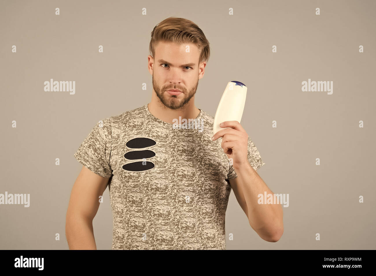 Man strict face holds shampoo bottle, grey background. Man enjoy freshness after washing hair with shampoo. Hair care and beauty supplies concept. Guy with hairstyle holds bottle shampoo, copy space. Stock Photo