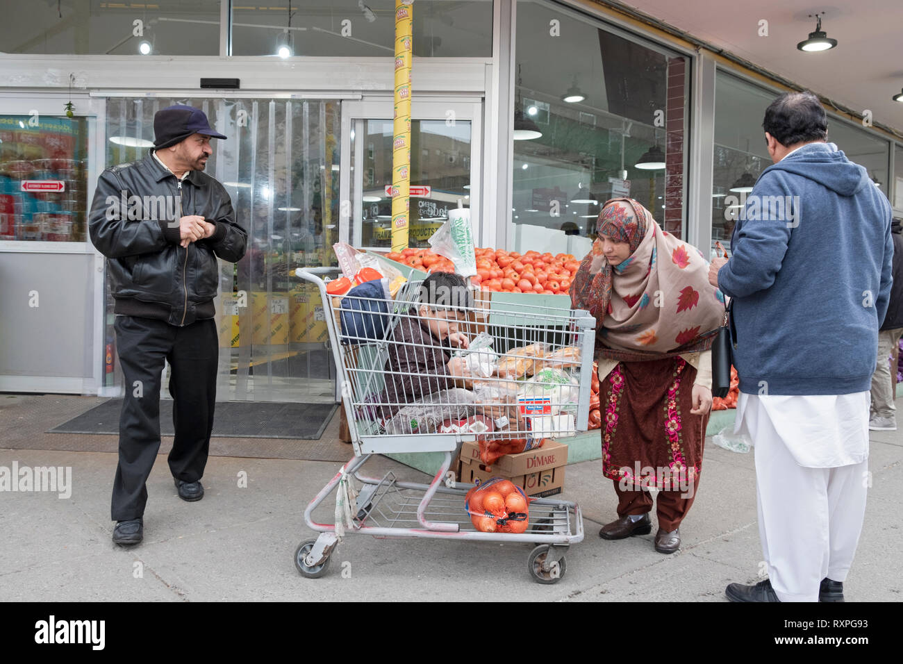 A scene outside the Apna Bazaar supermarket with a family & child in a shopping cart.  In Jackson Heights, Queens, New York City - Stock Image