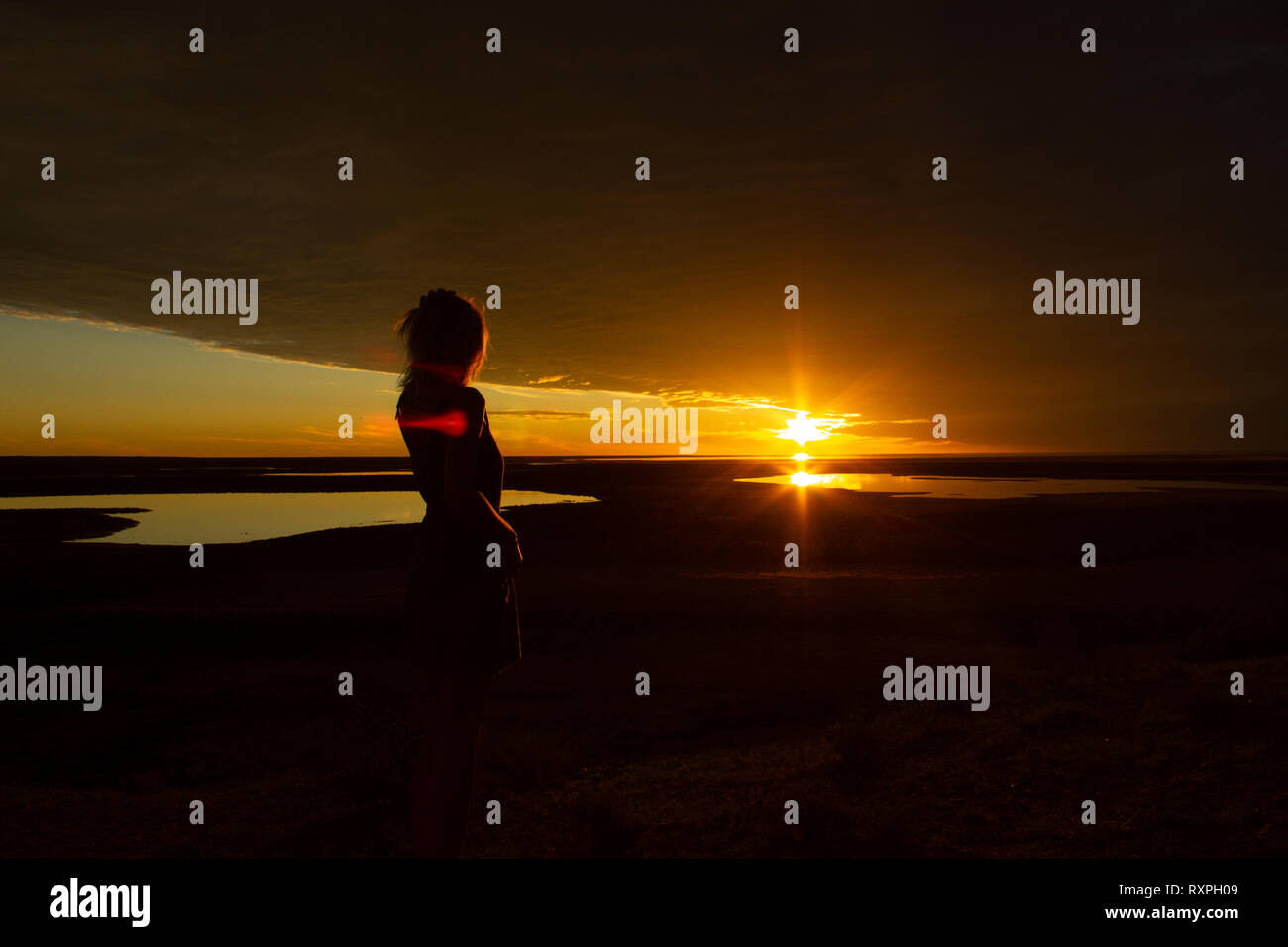 jung women enjoying beautiful sunset in the australian outback with 3 lakes, Gladstone scenic lookout, Australia - Stock Image