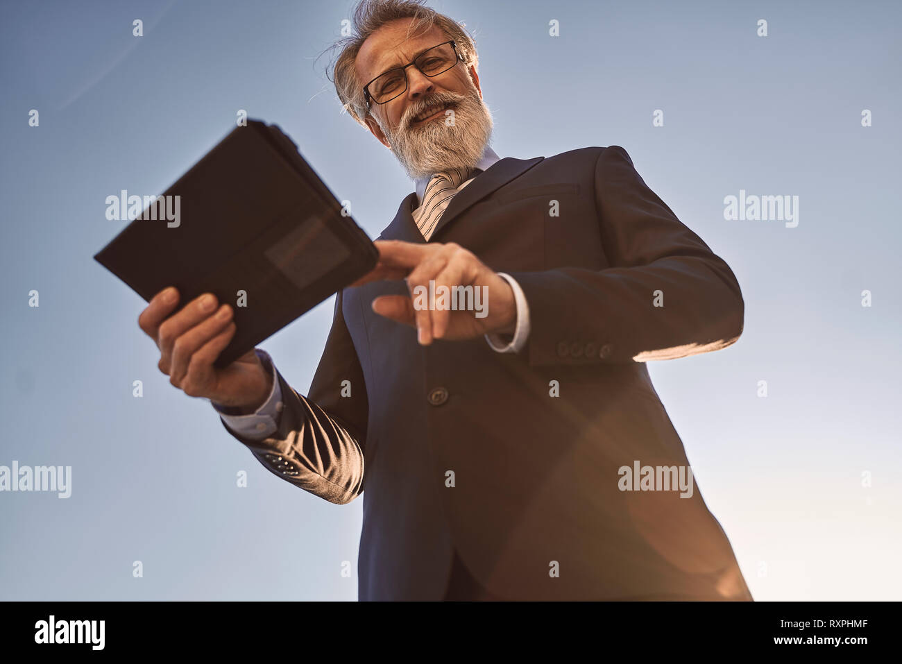 caucasian senior CEO using a smartphone and smart tablet while posing for the camera - Stock Image