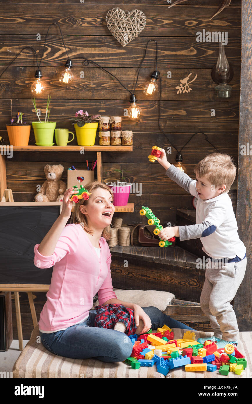 Educational game concept. Mom or nursery teacher and cute blond boy play with constructor details, plastic blocks on cushions. Mommy and standing - Stock Image