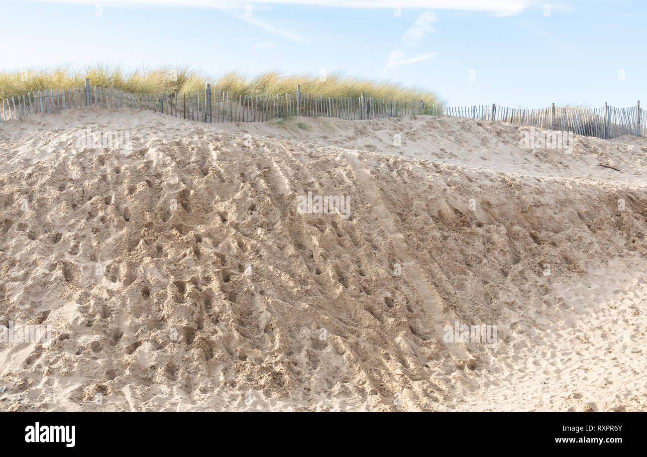 Sand dune with footprints, grass and fence at St Annes on Sea Fylde Coast February 2019 Stock Photo