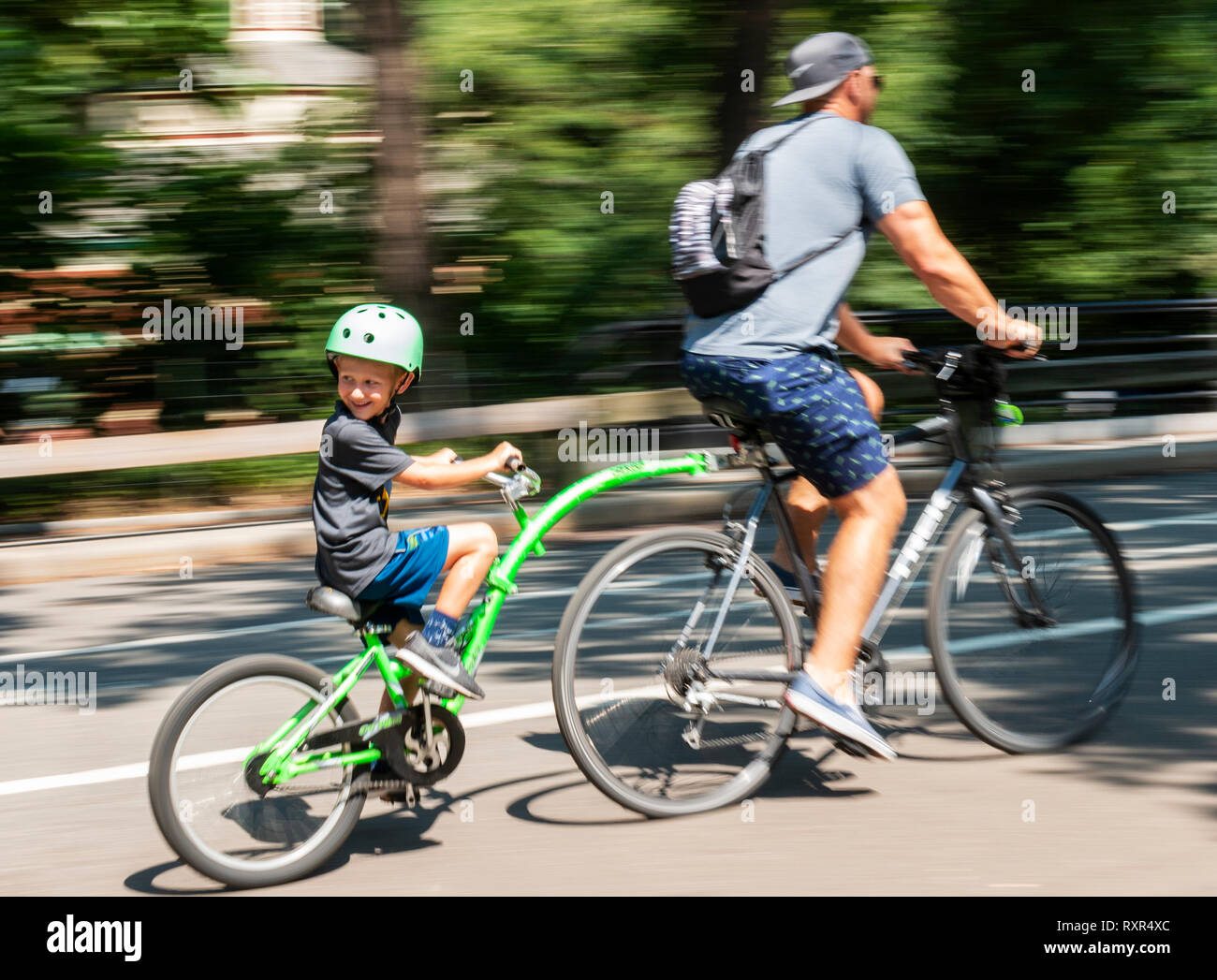 New York City, USA - 15 August 2018: Father and son riding a bike with an attachment on the back in central park with a blurred background. - Stock Image
