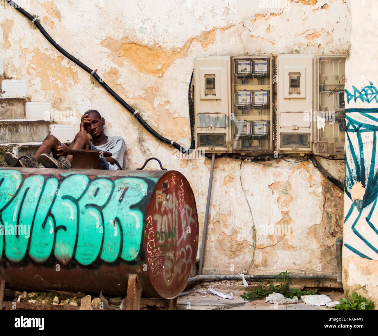 Havana, Cuba - 25 July 2018: A Cuban man sitting on steps with his legs on an oil tank leaning against a building in the shade avoiding the heat. Stock Photo