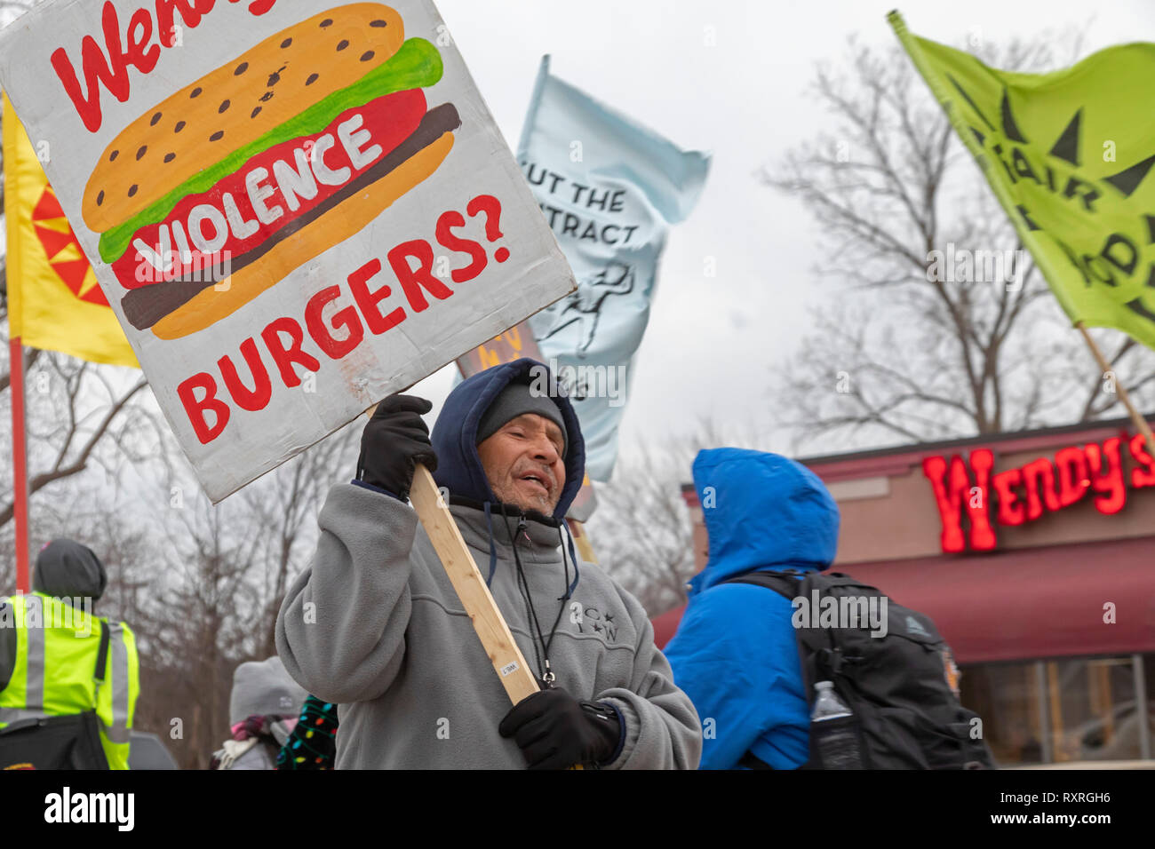 Ypsilanti, Michigan USA. 9th Mar 2019.  Members of the Coalition of Immokalee Workers and their supporters rally at a Wendy's fast food restaurant, asking the company to pay a penny a pound more for the Florida tomatoes it buys. The additional penny would go to improve wages for Florida farmworkers. The rally was part of a tour, targeting Wendy's stores in several university towns. CIW wants the universities to end their relationships with Wendy's until the chain joins the Fair Food Program. Credit: Jim West/Alamy Live News - Stock Image