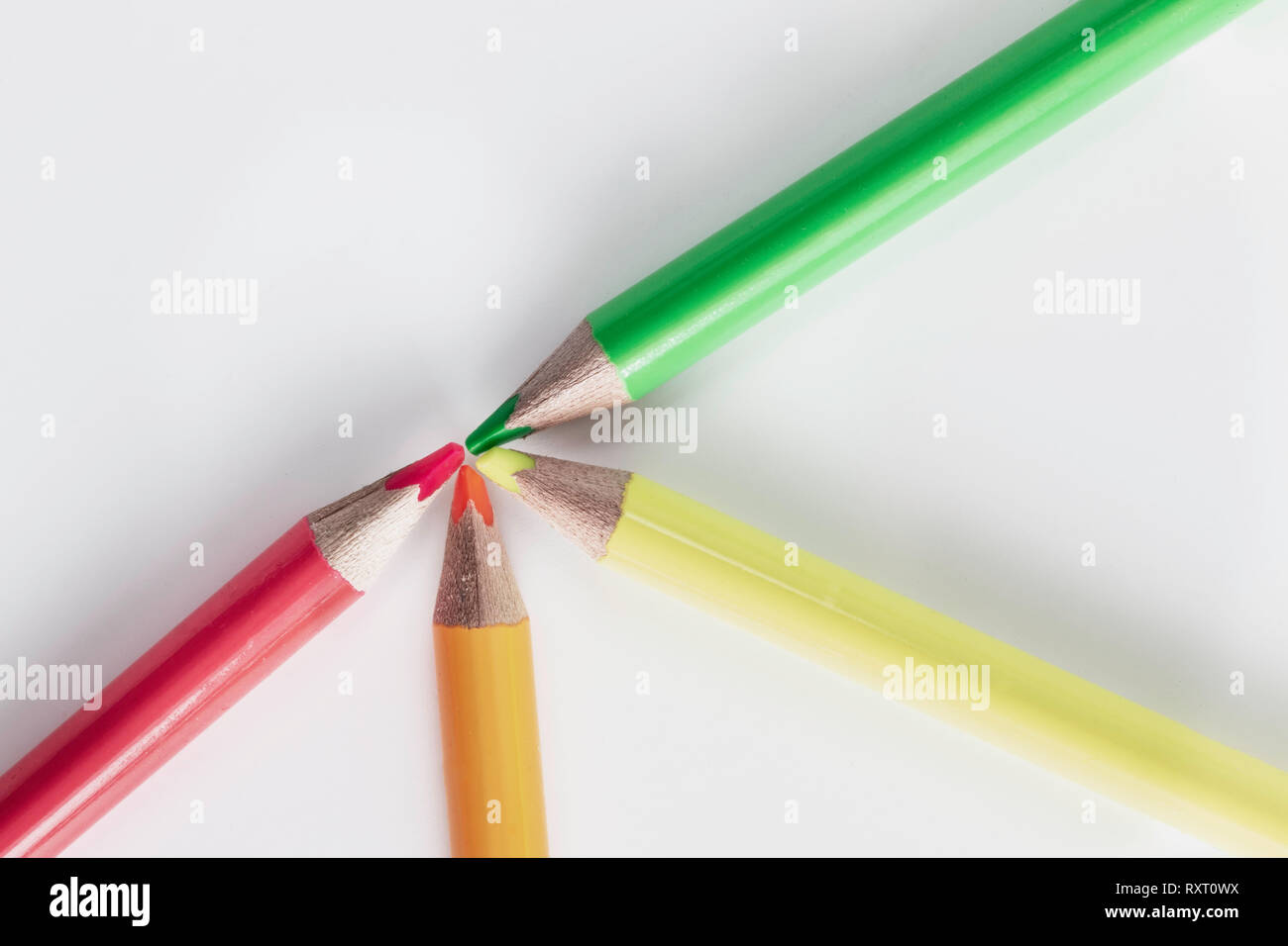 Four neon pencils crayons laid out on a white background - Stock Image