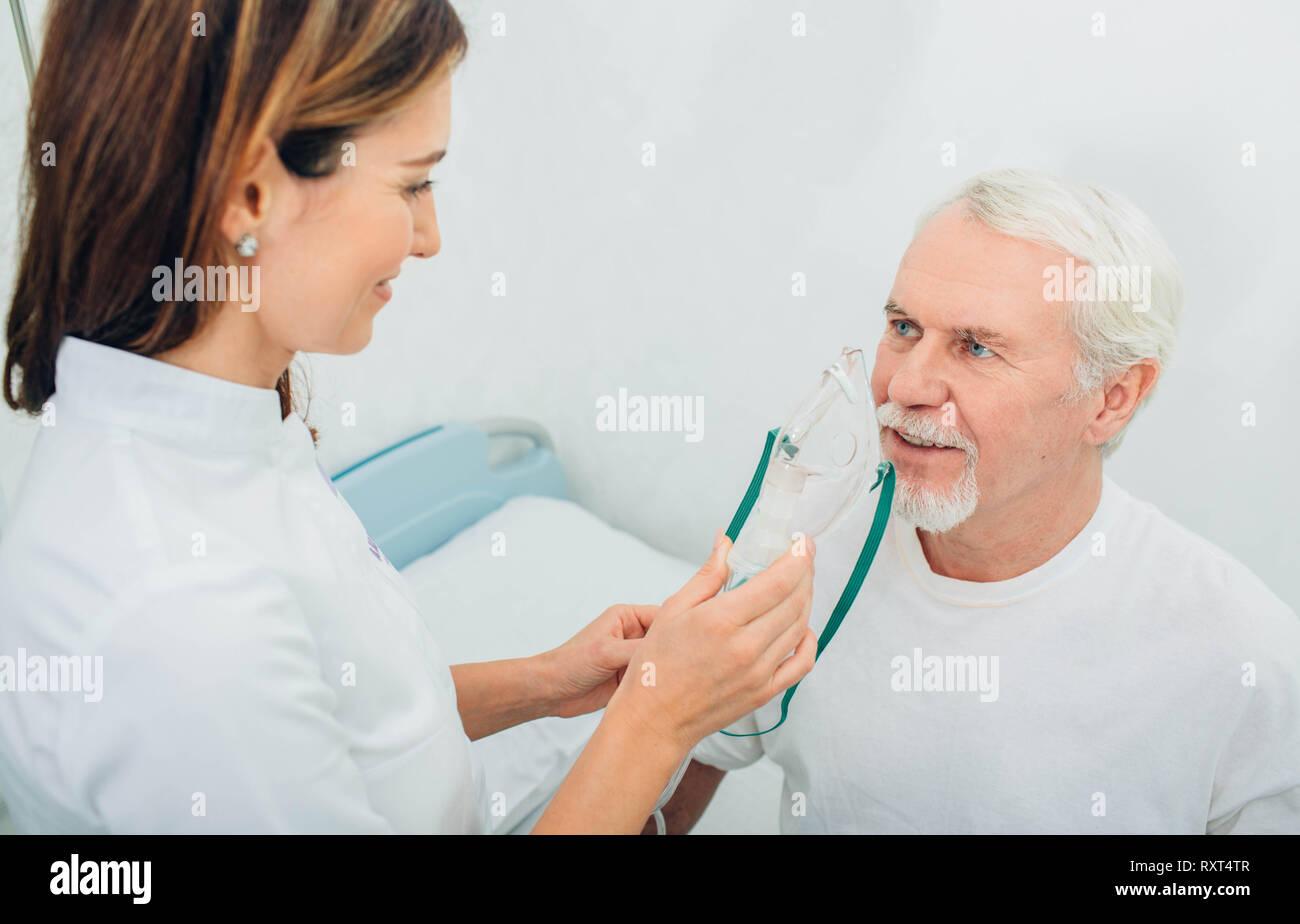 Senior man preparing to procedure inhalation at hospital - Stock Image