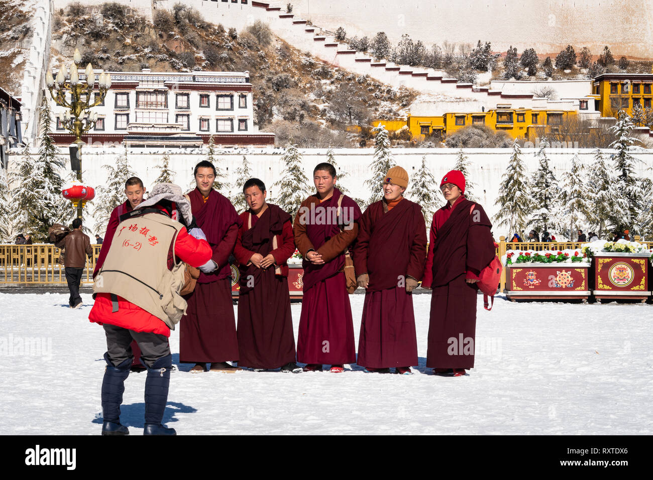 Lhasa, China - December 19 2018: Tibetan Buddhism monks posing for photo in front of the Potala Palace  on a sunny winter day in Tibet. - Stock Image