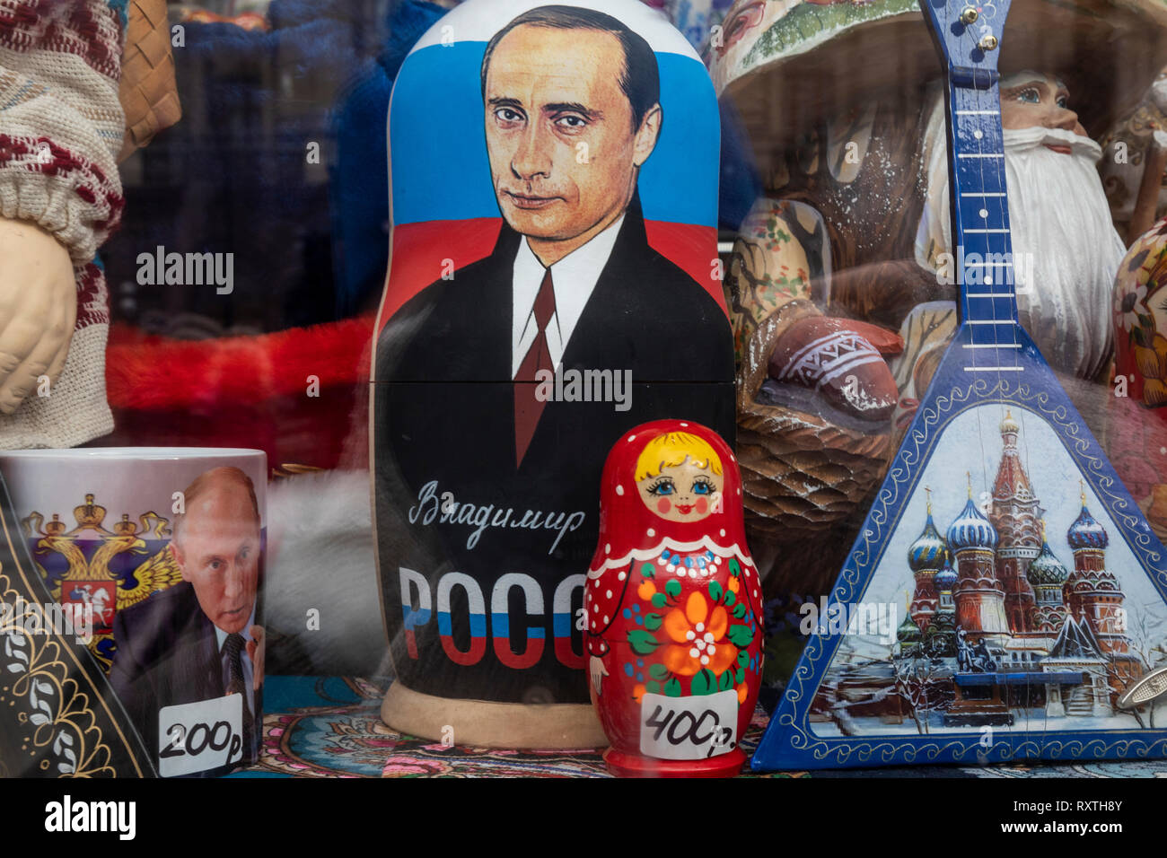 Russian traditional symbols - Matryoshka, Vladimir Putin portraits and balalaika in souvenir kiosk at central street in Moscow, Russia - Stock Image